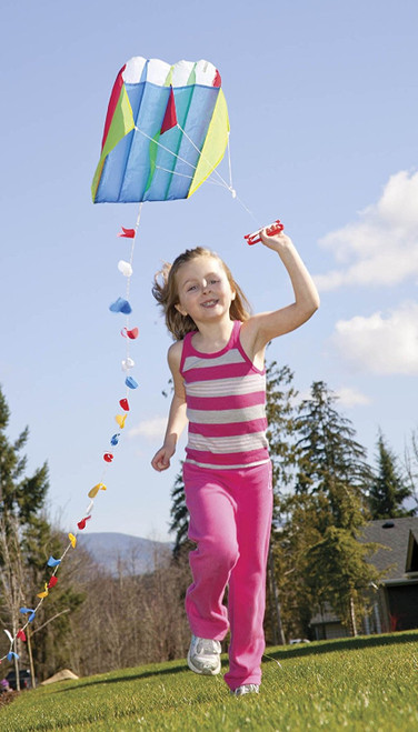 child flying a colourful parafoil kite outdoors, trees in background