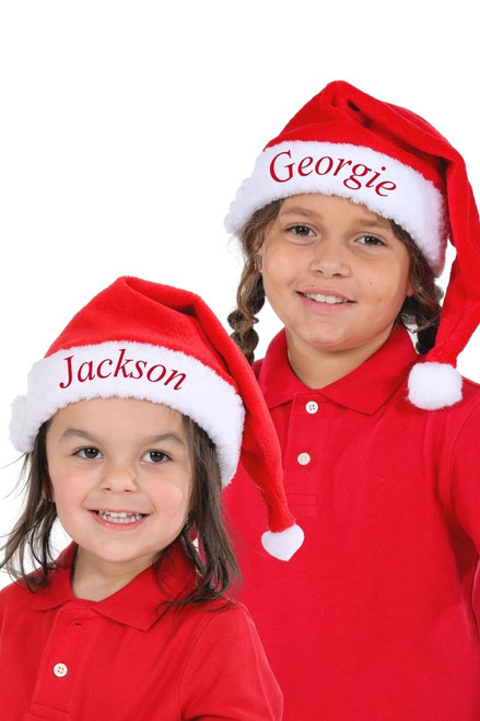 Two children are wearing Snug As A Bug personalized santa hats
