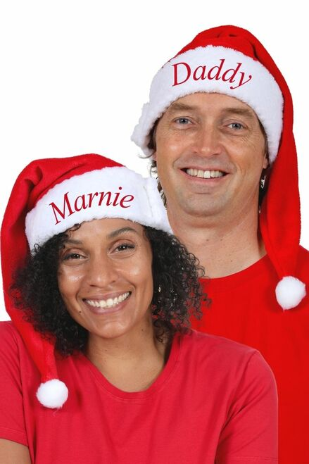 Two adults wearing Snug As A Bug adjustable Santa hats