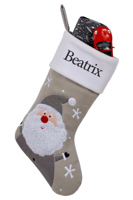 """Snug As A Bug Modern Grey Christmas stocking, Santa, is shown personalized """"Beatrix"""" and filled with gifts"""