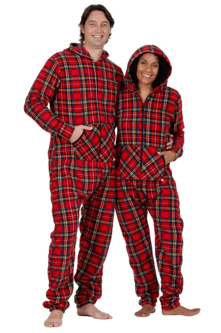 two adults are wearing matching footless red tartan onesie pajamas