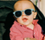 a baby wearing blue keyhole style babiators sunglasses