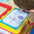 a child seated at a table is bent closed, absorbed in making art with spirograph jr. art set