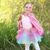 a child in a pink super hero costume is standing in a meadow, smiling at the camera