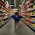 a child in a blue superhero cape is running down an aisle in a supermarket
