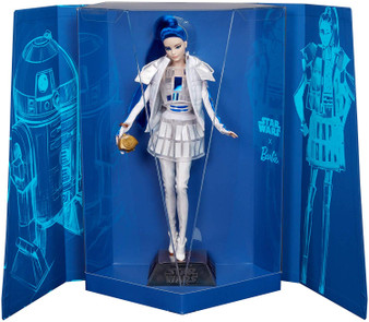 "The Star Wars x Barbie collaboration is an homage to Star Wars: A New Hope. This eponymous collection, inspired by the film's original concept art, re-imagines iconic characters through a distinctive Barbie high-fashion filter. This collectible Star Wars x Barbie doll captures R2-D2's look in a geometric ensemble with a dome skirt, bomber jacket and thigh-high boots over silvery tights. A vibrant blue ponytail and ""radar eye"" detail complete the look. Star Wars R2-D2 x Barbie Doll includes a Star Wars doll stand and Certificate of Authenticity."
