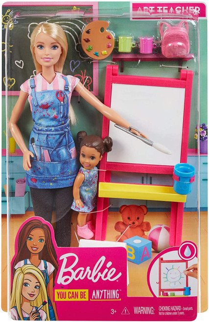 """You can be an art teacher with the Barbie Art Teacher playset Includes art classroom environment with Barbie Art Teacher doll, her adorable toddler student doll and toy art play pieces for learning and creative expression. Barbie Art Teacher shows her adorable student how to paint at the easel with a fun colour-change surprise: dip the brush (included) in water and paint over the blank surface and the painting magically appears Create again and again by wiping off the surface. Wearing leggings, a T-shirt, tennis shoes and a cute denim art smock, Barbie Art Teacher doll is ready to teach her eager-to-learn toddler student doll, who wears a cute dress and carries a backpack Toy play items include an easel and painting surface, paint and water """"containers,"""" palette, brush and toddler step stool."""