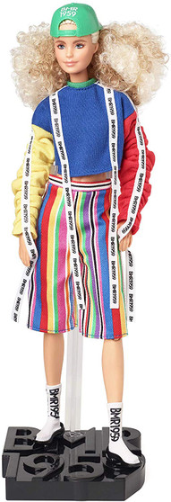"""BMR1959 celebrates the 60-year fashion legacy of Barbara """"Barbie"""" Millicent Roberts with a collection that's all about self-expression and personal style. Bold, fully poseable BMR1959 dolls capture what's trending in streetwear, from high-low fashion mixes, re-imagined '90s gear to juxtaposed patterns, textures, and silhouettes. This BMR1959 doll wears a color-blocked crewneck sweatshirt with logo tape and bright, striped shorts. Logo-print sock sneakers and a green baseball cap worn over her curly, blonde hair complete the look. Specially designed, FSC-certified shoebox packaging is made from materials that have been responsibly sourced."""
