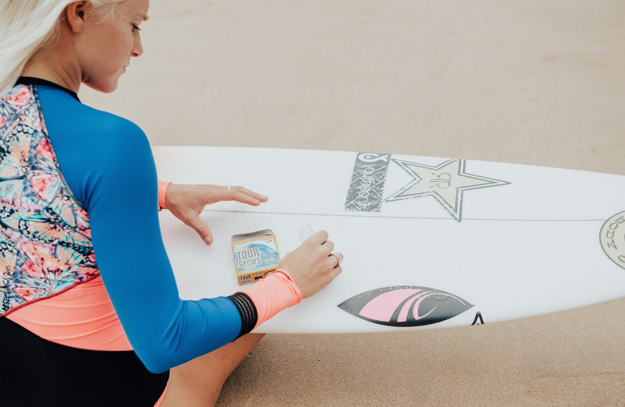 tatiana weston-webb using sticky bumps wax to wax surfboard