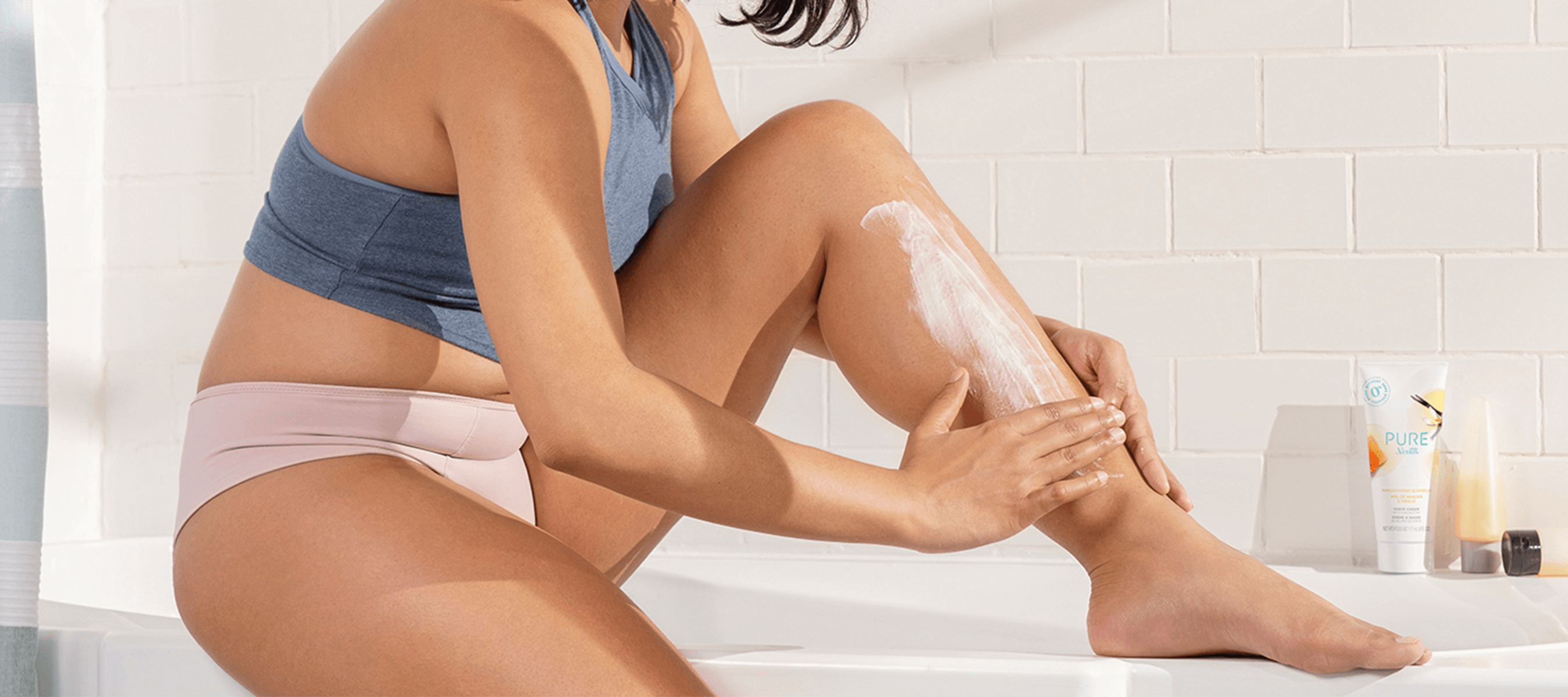 Woman applying shaving cream to leg while sitting in a bathtub.