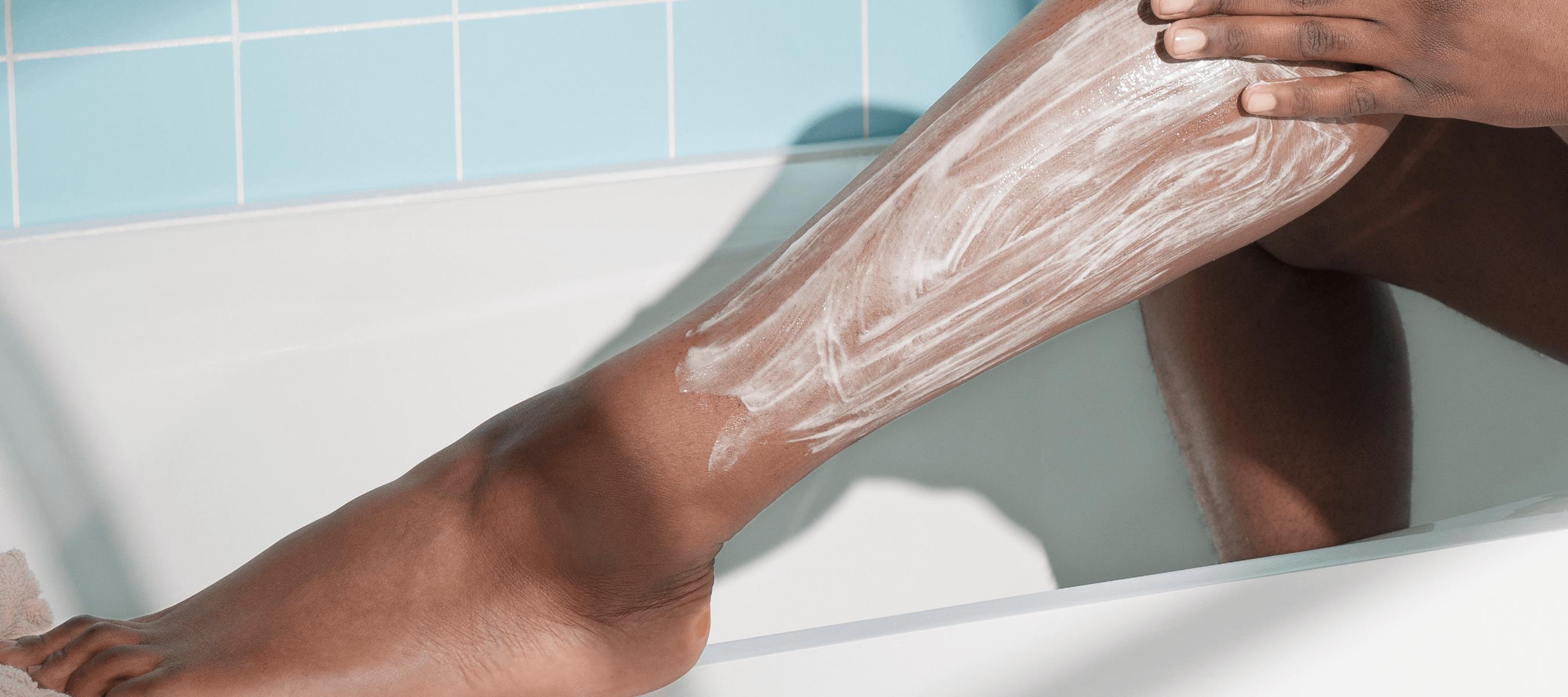 having cream on a woman's leg in a bathtub.