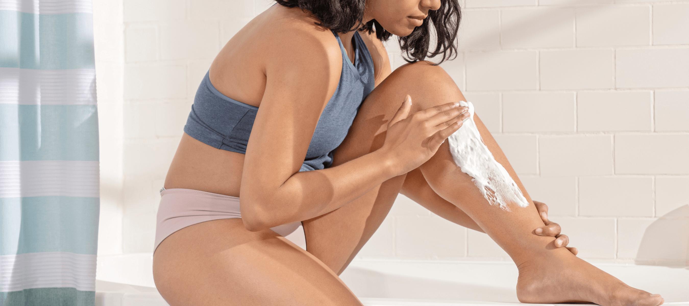 Woman applying shaving cream to her leg before shaving.