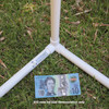 An example of how a 20mm 3way elbow connector fitting from Klever Cages is used on grass with a $10 note as an example for size. PVC projects that can be built with the 3 way 20mm fitting include cat enclosures, chicken tractor, kids indoor cubby house, garden protection, frost protection and more.