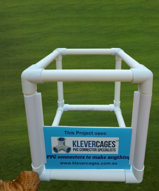 Cube built with PVC connectors 3 ways and snapframe with a corflute sign with a grass background
