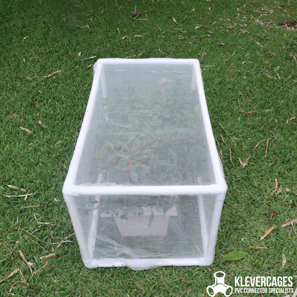 Herbs including mint thriving in a long cream self watering pot from Bunnings sitting on the grass protected from pests including insects and birds with the fine mesh netting supported by a 20mm PVC pipe and white PVC fittings from Klever Cages