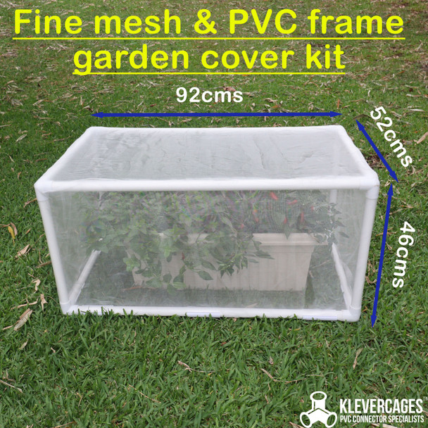 Side view of a fine mesh netting on a PVC pipe and Klever Connector frame protecting some mint and chilies from pests including birds and insects in a self watering pot from Bunnings, sitting on the grass.