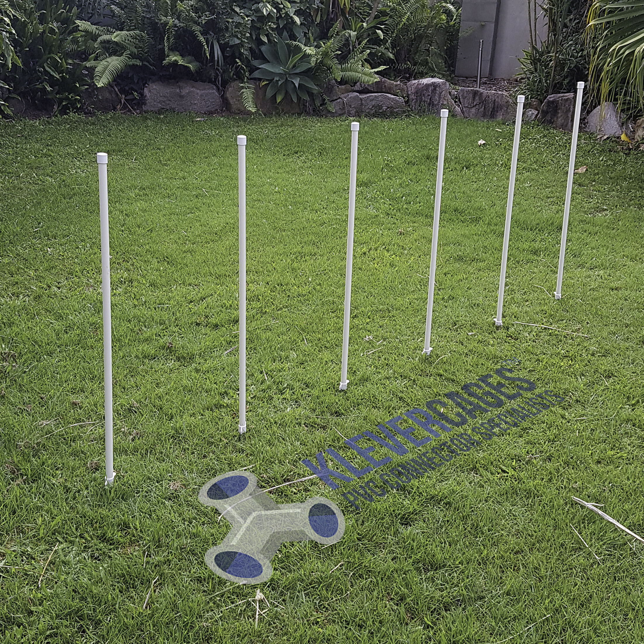 6 dog agility weave poles available in a kit for a agility course. White  PVC pipes caps and stakes from Klever Cages Australia