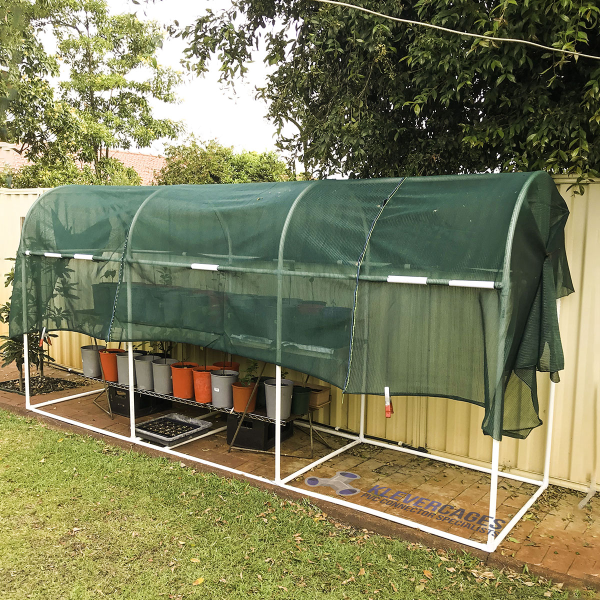 Easy to build arched shadehouse frame covered with green shadecloth built with a PVC pipe and connector frame to protect pot plants from the harsh sun. PVC connectors used are 20mm l-tees, 3 ways, tees, slip tees and snapclamps from Klever Cages Australia