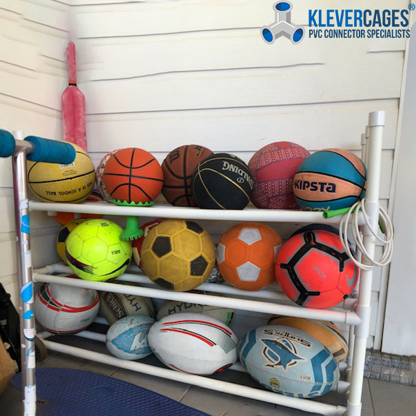 Ball rack storage built with PVC pipe and connectors from Klever Cages. Balls include basketball, soccer ball and rugby ball.