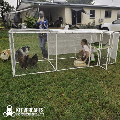 Chicken tractor built with PVC connectors including 3 ways, ltees and pipe from Klever Cages. On grass with chicken wire and dogs watching