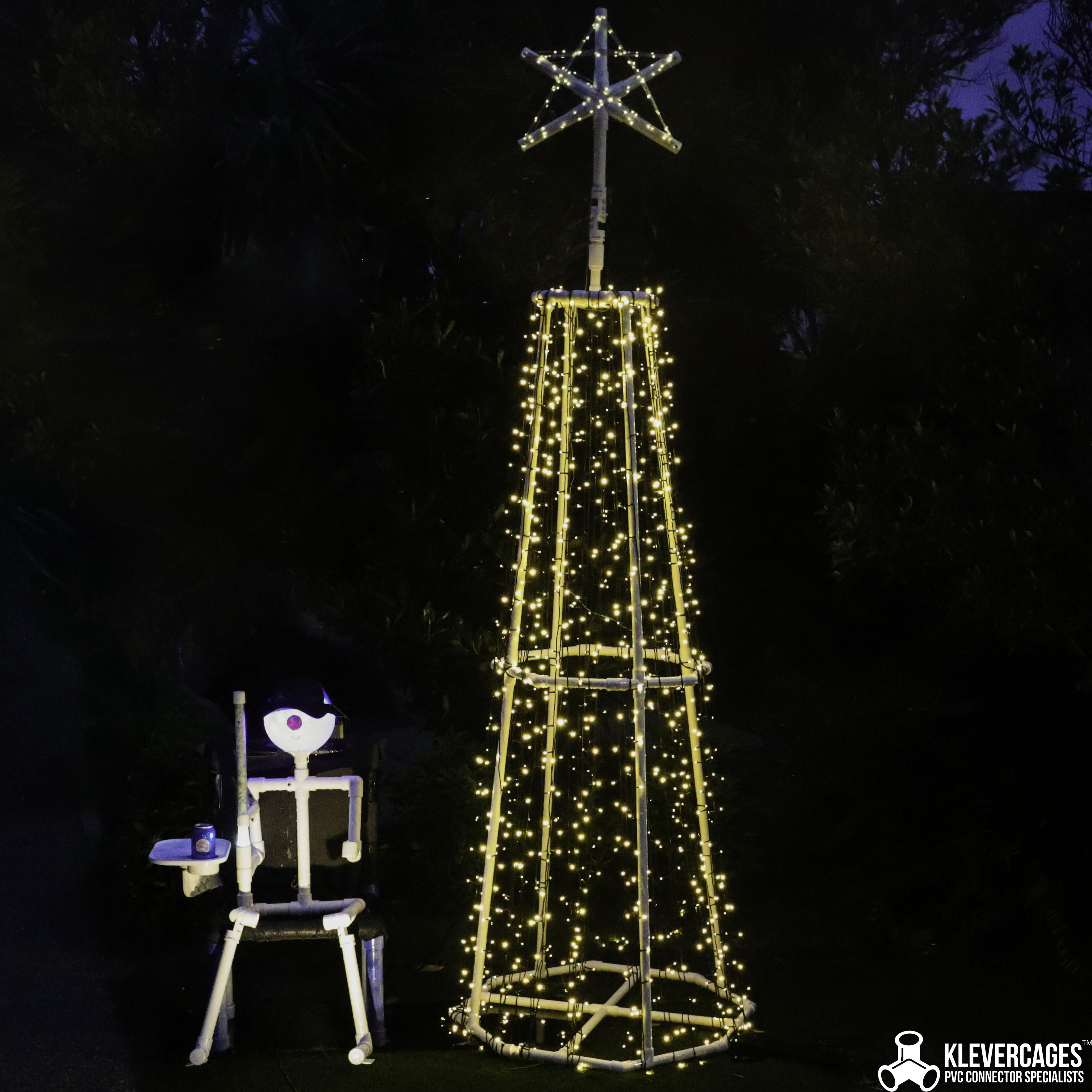 Connector Cam PVC pipe person sitting on a chair in the dark guarding a christmas tree. Cam is built from 25mm connectors and PBVC pipe from Klever Cages
