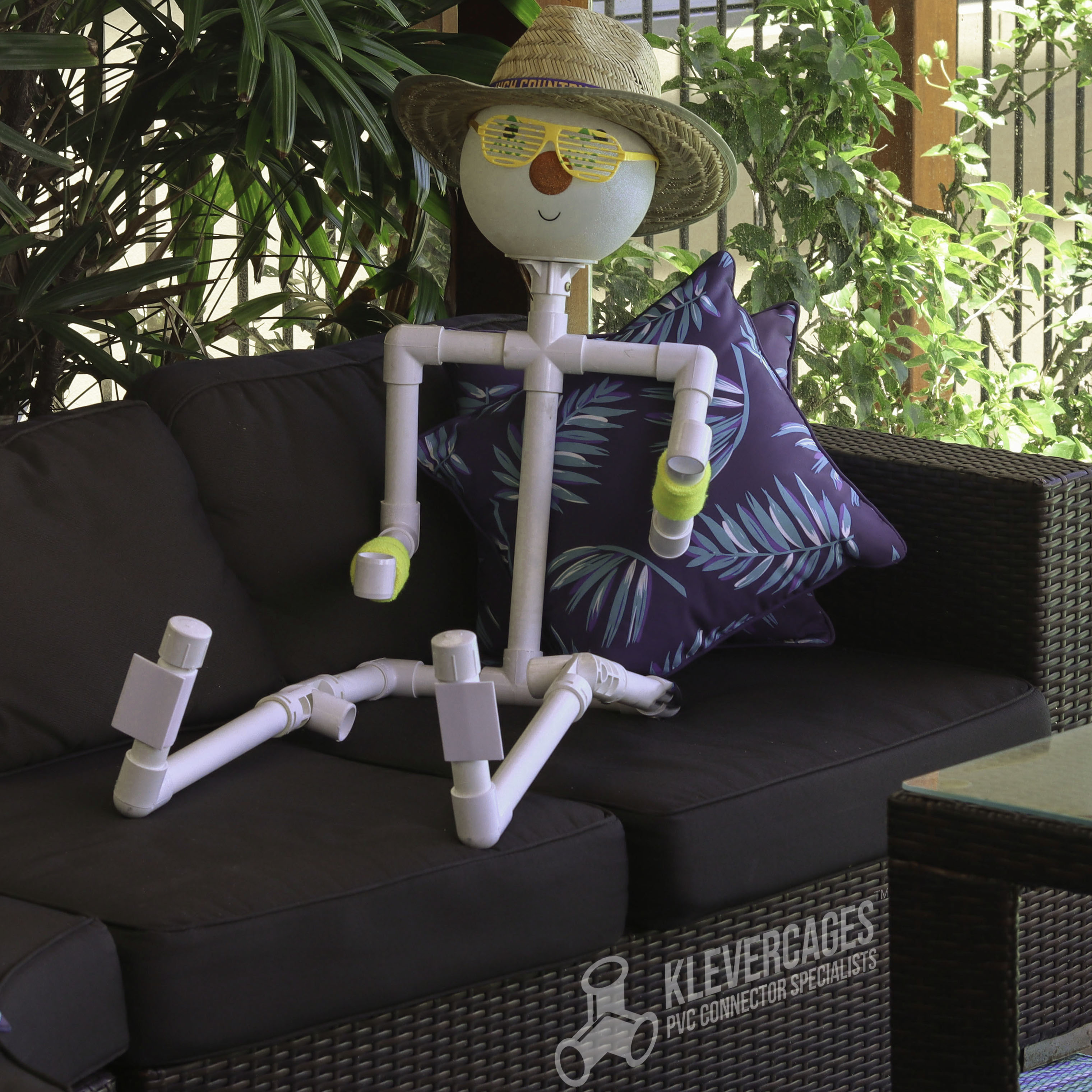 Connector Cam (PVC pipe person) built from elbows, crosses, sliptees and more connectors and PVC pipe sitting on a lounge relaxing with a hat on