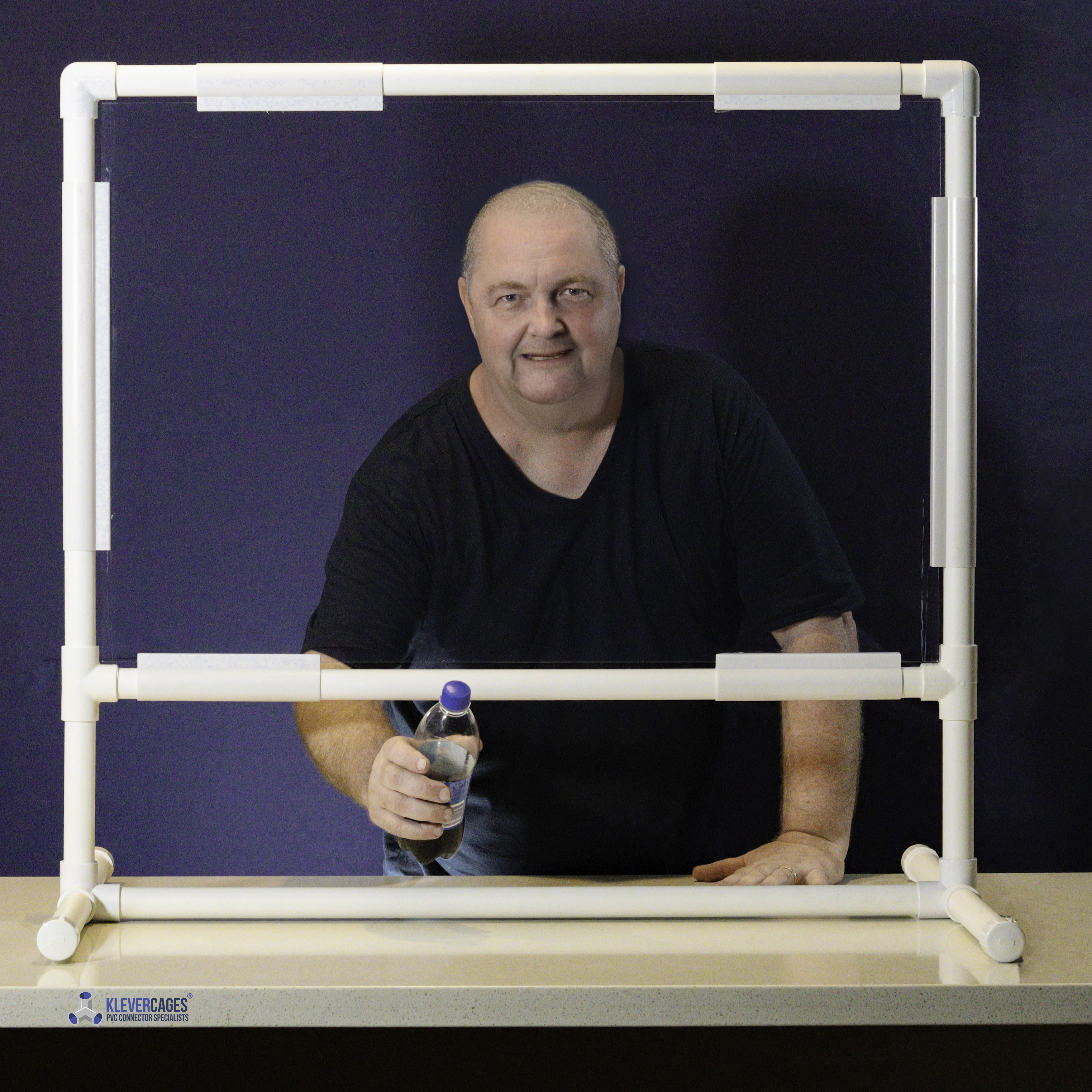 shop attendant serving a drink while behind a Perspex screen supported by PVC pipe and connectors from Klever Cages.