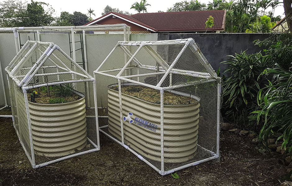 Frames protecting garden using PVC connectors and pipe including, 3 ways, ltees, and tees. Hinged lid for easy access.