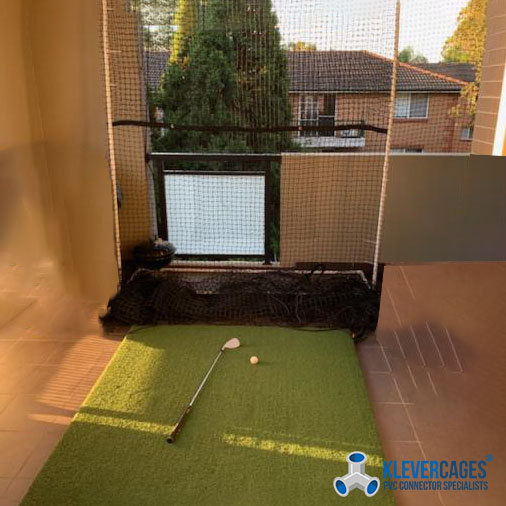 Golg practice net frame on a balcony with a gold ball and club