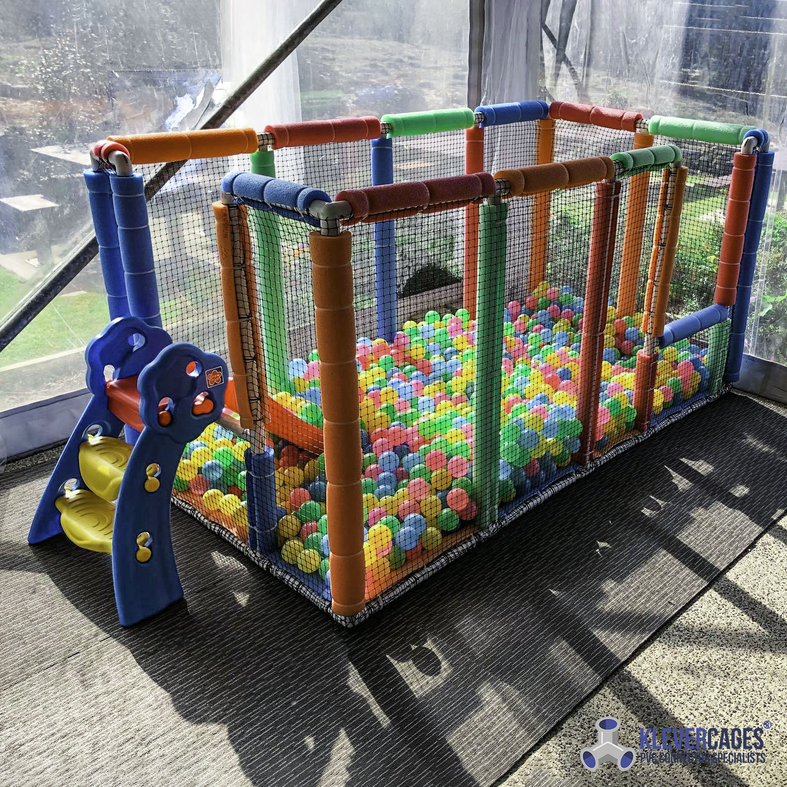 Kids indoor ball pit with stairs padded with pool noodles built with PVC pipe and 3 way connector fittings from Klever Cages