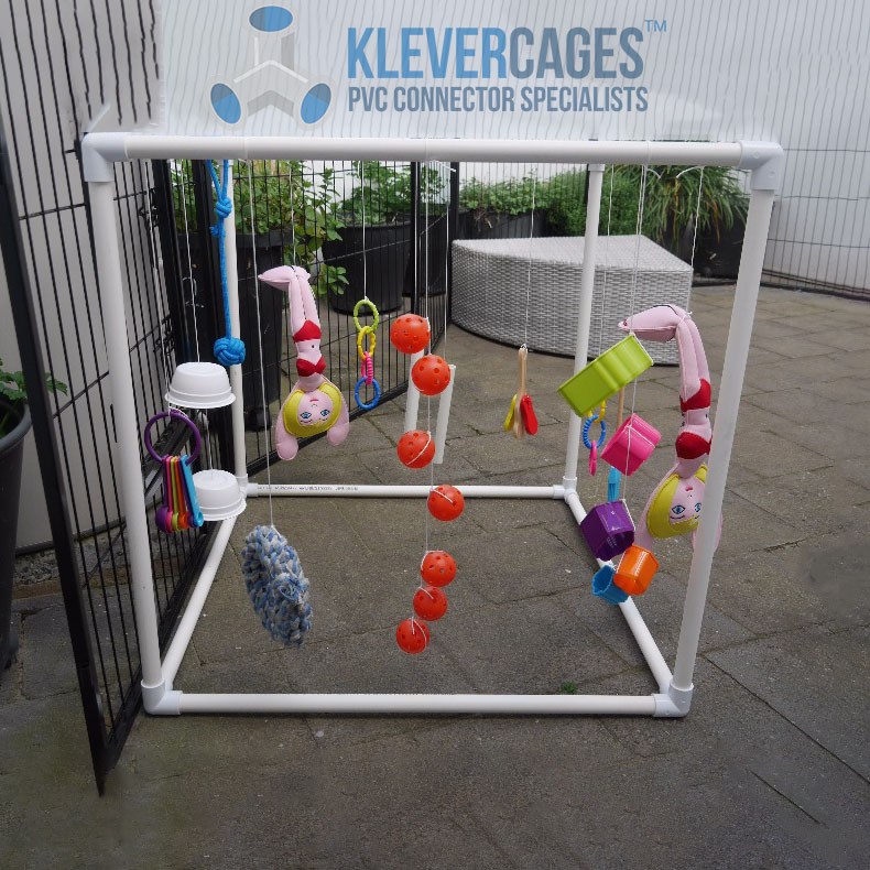 Puppy play gym built with 3way PVC connectors and pipe from Klever Cages. Dog toys hanging from frame in the backyard on pavers.