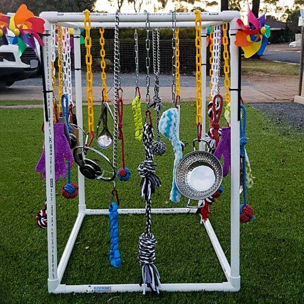 Easy DIY puppy play gym built with PVC connectors and pipe from Klever Cages Australia. Dog toys hanging on plastic chains.