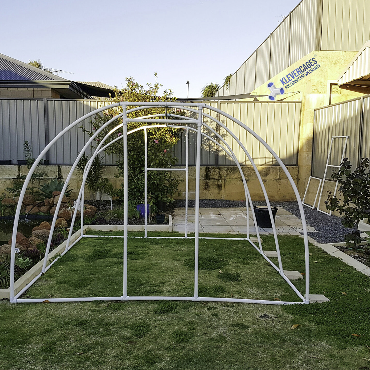 Walk in Greenhouse frame in the process of being built in the backyard. Frame is made from PVC connectors 25mm tees, hinges, 3ways and slip tees from Klever Cages Australia