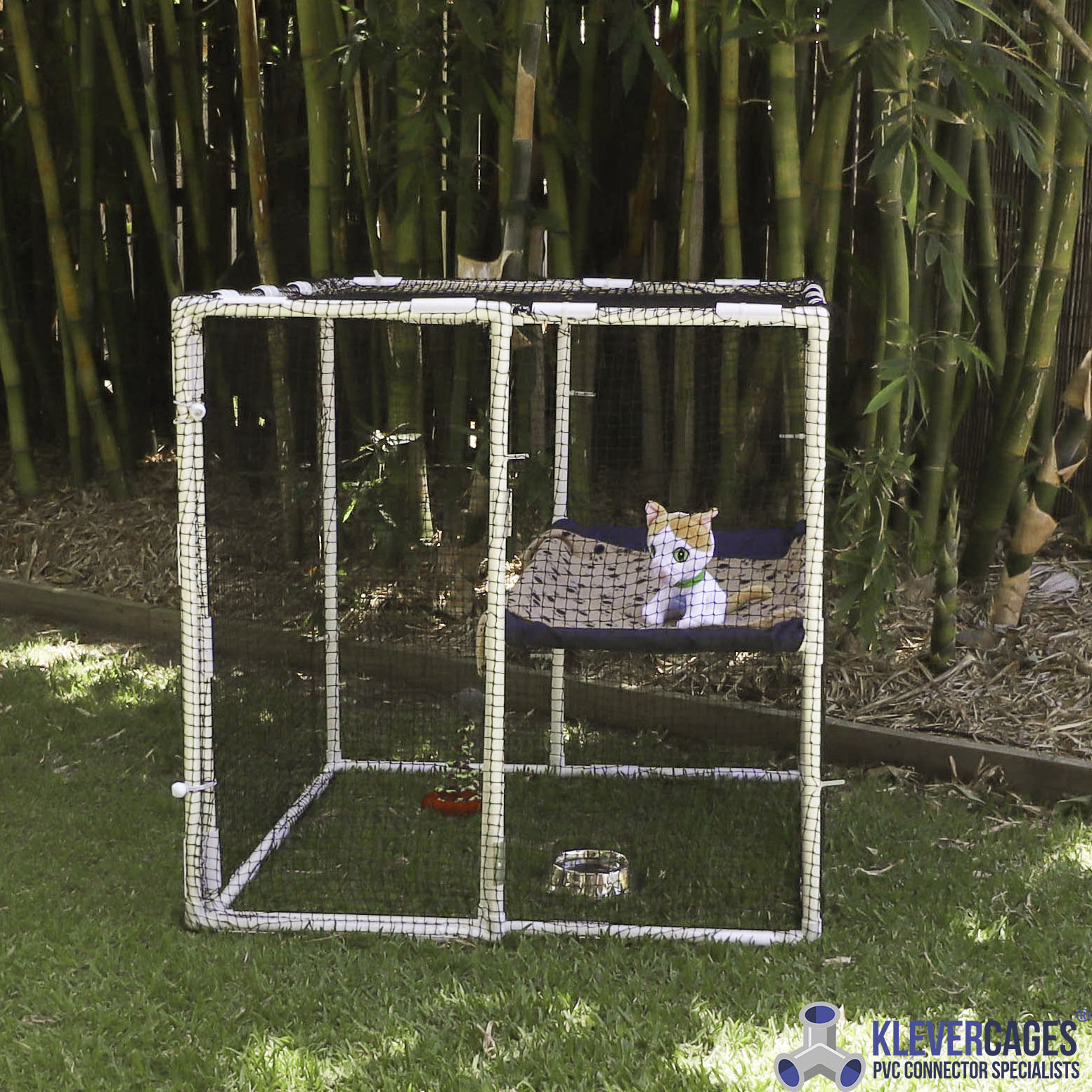 Small cat enclosure catio built with PVC pipes and Klever Connectors from Klever Cages Australia. This cat enclosure is outside on the grass infront of bamboo