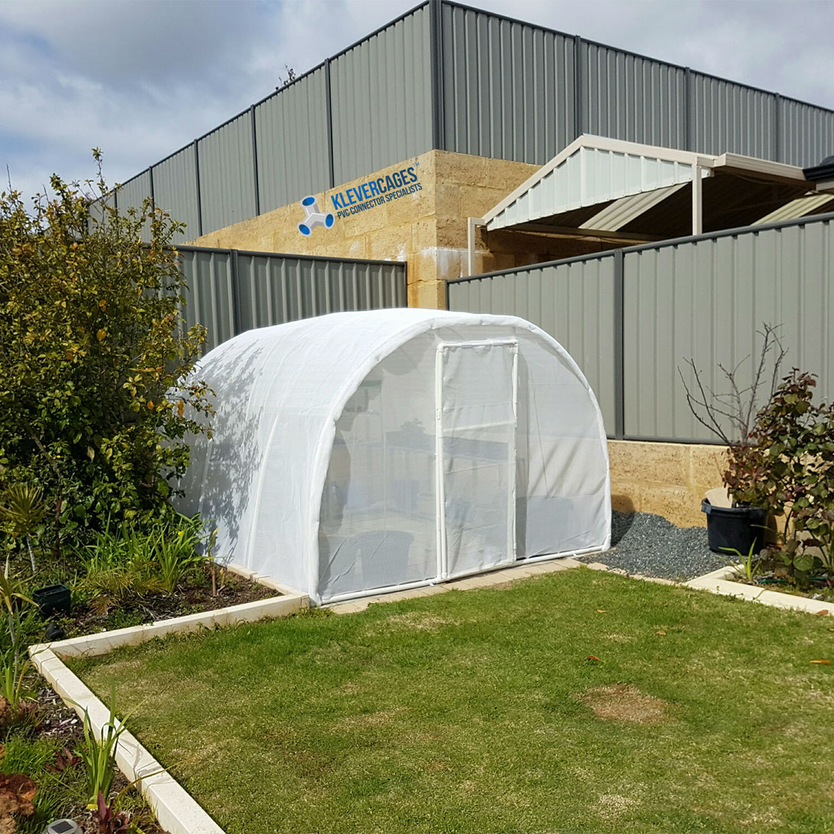 Walk in white arched greenhouse frame covered with plastic, built with PVC connectors and pipe in the back corner of the backyard