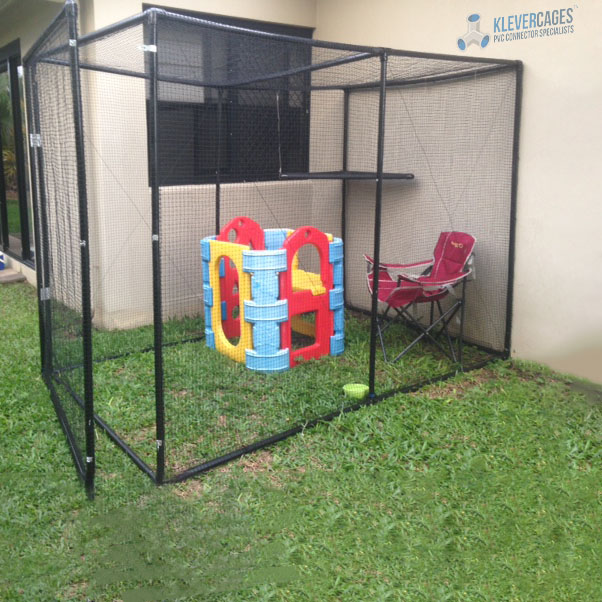 Walk in cat enclosure with a hinged door and black PVC pipe and connector frame. A folding chair and some play equipment sitting on the green grass