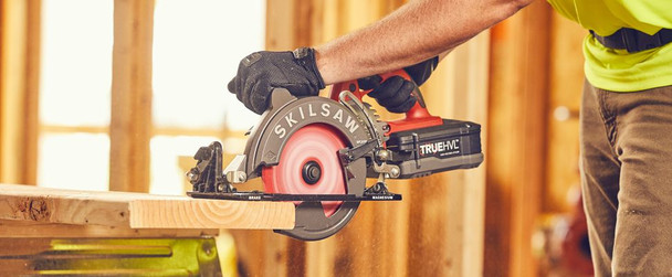 """Worker using Skilsaw 7-1/4"""" TRUEHVL Cordless Worm Drive Saw Bare Tool to cut wood plank"""