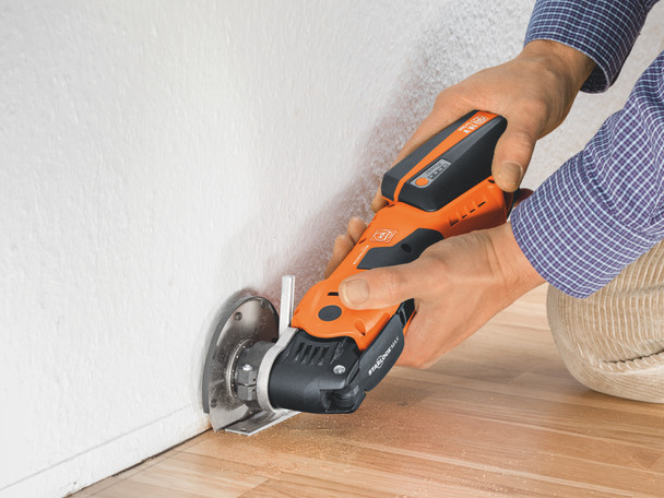 Fein cordless multimaster AMM 700 max top cutting wood against a baseboard