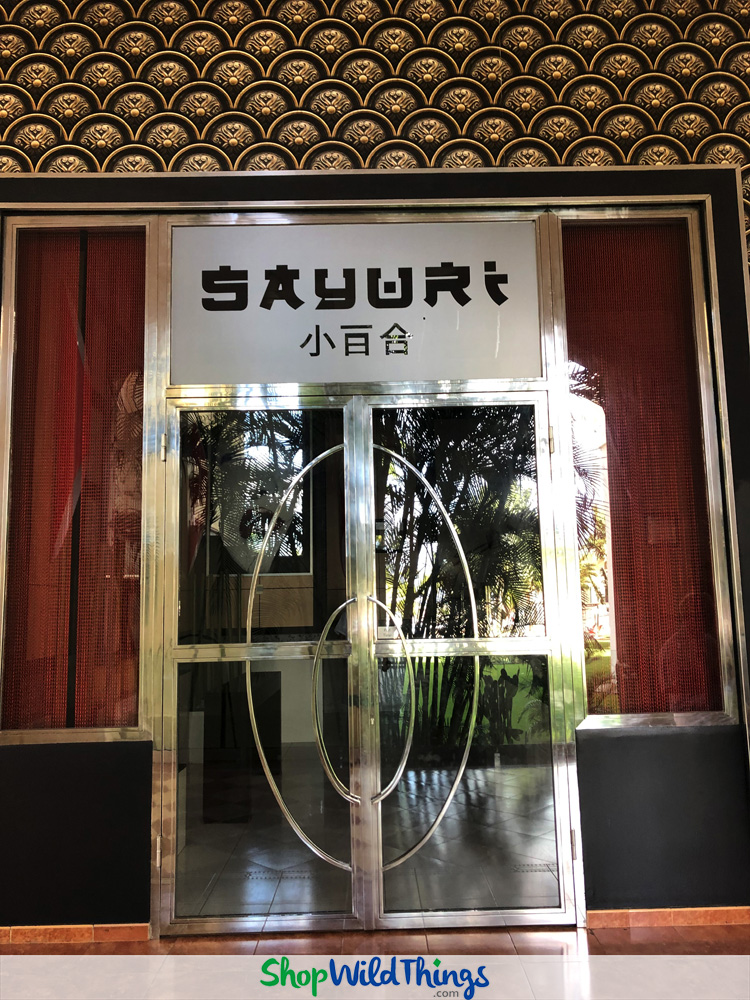 Upscale Retail & Restaurant Decor Features Metal Chain Curtains & Greenery Walls