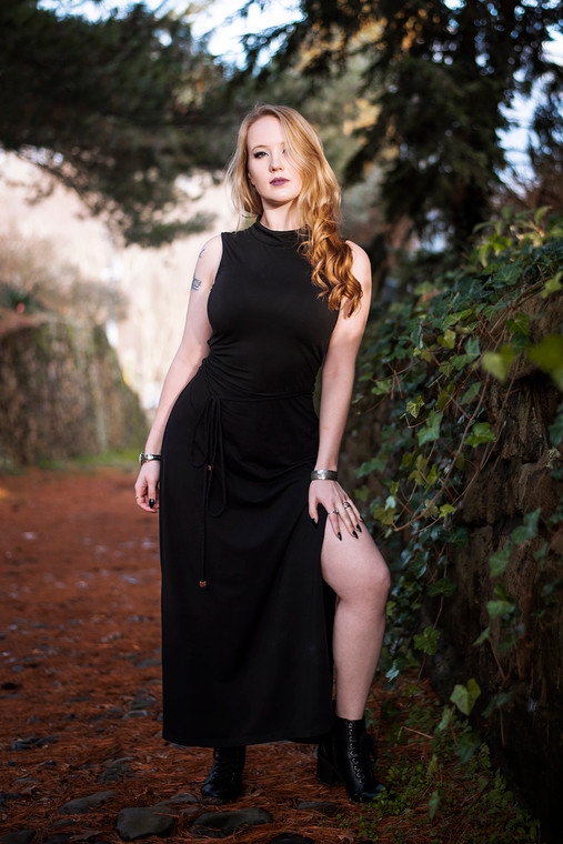 Long black maxi dress with beaded waist ties and thigh slit.