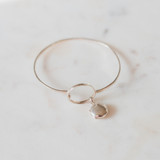 silver bangle bracelet holds one or two photos on a white marble table