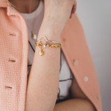 woman wearing gold and silver bangle with charm bracelet for layering look.  Pink coat is worn over the shoulders.