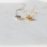 two closed lockets, bottom view, laying on a white table.  silver and gold.