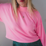Woman with one arm up, wearing a pink sweater, red lipstick, and a simple sterling silver oval pendant locket necklace