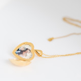 photograph of woman and two children inside gold heart locket on white marble