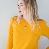 gold heart locket on an 18 inch chain on a woman wearing a yellow dress