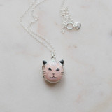 closeup of the pink meow meow cat locket with black ears and pink enamel