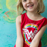 little girl in red wonder woman shirt wearing a pink cat locket