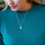 woman in green sweater wearing a cat locket that holds two photos inside