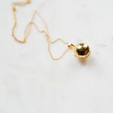 gold round locket on marble backing